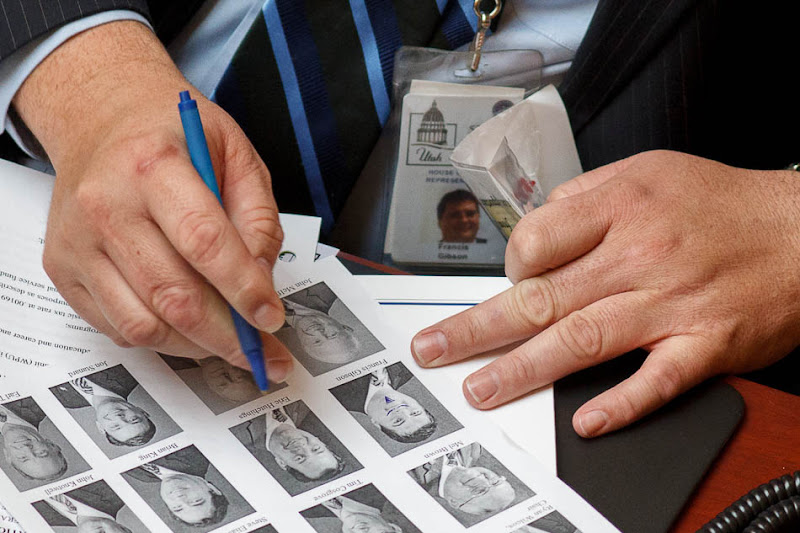 Rep. Francis Gibson draws a doodle on his own photograph in a House roster in the House chamber on the second day of the Utah legislative session in Salt Lake City