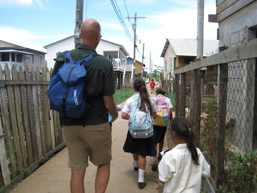 Erik helping a school girl carry home a water jug, Utila, Honduras