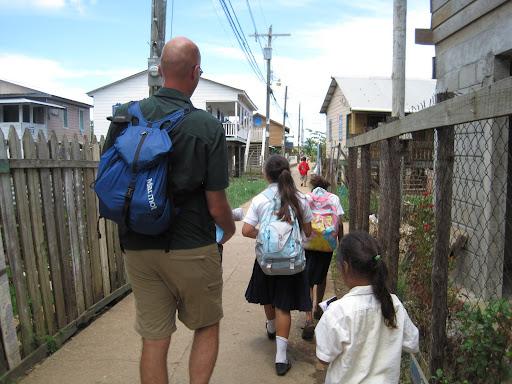 Erik helping a school girl carry home a water jug, Utila, Honduras