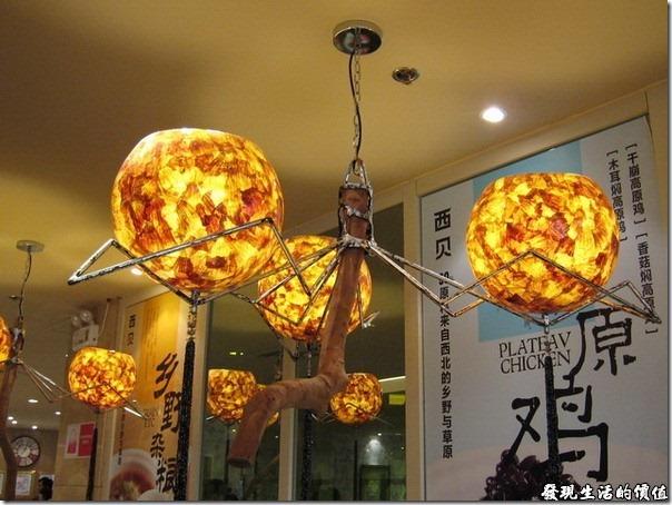 上海-西貝攸面村。餐廳的裝潢擺設也有別於一般的餐廳,雖然不是什麼高級餐廳的擺設,但看起來還是別具特色,尤其是它的吊燈,使用天然木頭與鐵架支撐三顆琥珀色的燈罩。不過似乎也不是每家「西貝莜面村」都有一致的裝潢。