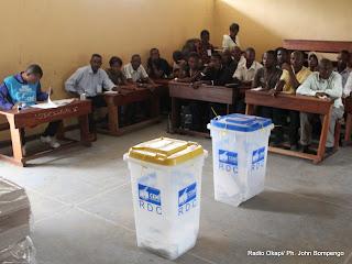 Des témoins des candidats devant les urnes le 28/11/2011 dans un bureau de vote au quartier Makelele dans la commune de Bandalungwa à Kinshasa, pour les élections de 2011 en RDC. Radio Okapi/ Ph. John Bompengo