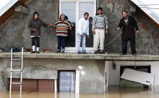 People stand on a terrace of their flooded house as the wait to be evacuated in the town of Obrenovac, east from Belgrade, 17 May 2014. Photo: Reuters