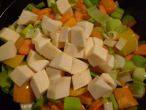 Vegetables cooking in the pan and on top, chunks of peeled, white sweet potato.