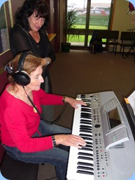 Delyse Whorwood practising on her Technics KN6500 whilst new member, Eileen Grainger, studiously watches on.