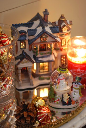 Christmas ornaments and candle on mirror