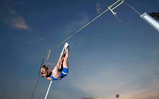 Strong Athlete Pole Vaulting at Track and Field Event