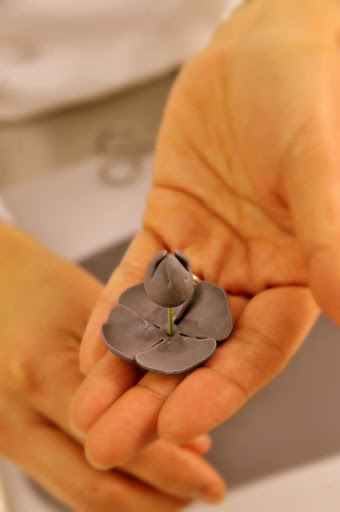 Ana threads the delicate petals onto the stem.