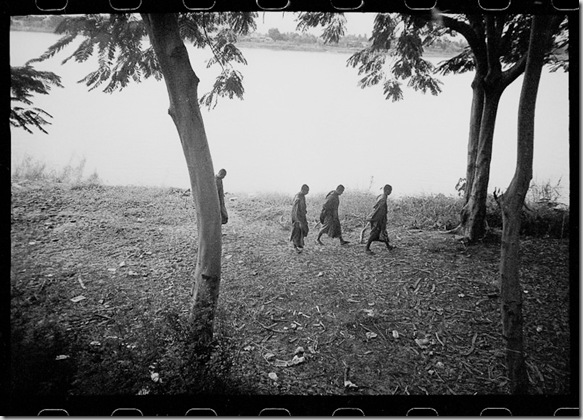 Monks walk along the Mekong River in northern Thailand