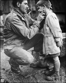 American soldier Walton Trohon cleaning the face of a young French orphan, France, 25 November 1944
