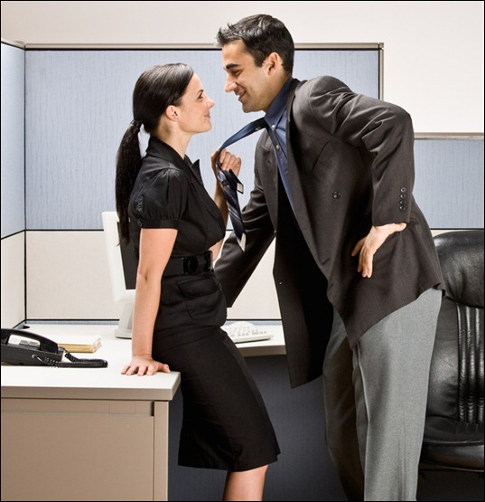 Co-workers kissing in office cubicle