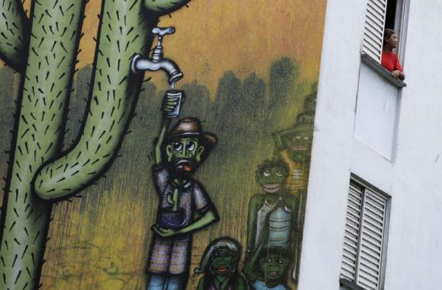 A resident looks out of her apartment in a building painted with a drought-related mural, painted by Brazilian artist Mundano, depicting a man getting water from a cactus plant, in Sao Paulo, 25 November 2014. Photo: Nacho Doce / Reuters