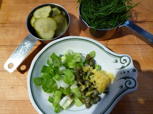 Scallions, capers, lemon zest, pickle slices, and dill are ready for the food processor.
