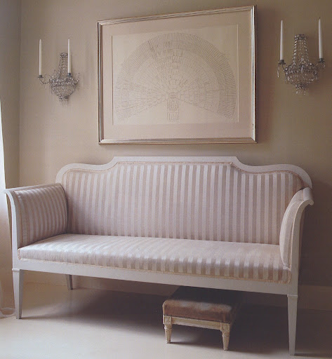 The sofa is upholstered in shades of silvery taupe and beige, and on the wall, crystal sconces and a silver frame further enhance the gleam.