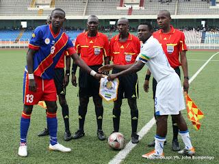 De gauche à droite, le capitaine de l'équipe de la RDC et celui du Gabon échangeant de fanions ce 30/04/2011 au stade des martyrs de Kinshasa, devant les quatre arbitres de la rencontre, lors des éliminatoires des jeux africains Maputo 2011 (RDC 1 - Gabon 0).