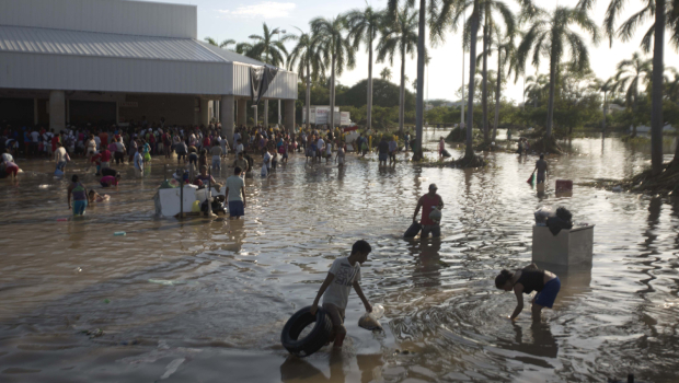 People wade through waist-high water in a store's parking lot in Punta Diamante, south of Acapulco, Mexico, Wednesday, 18 September 2013. Photo: Eduardo Verdugo / AP