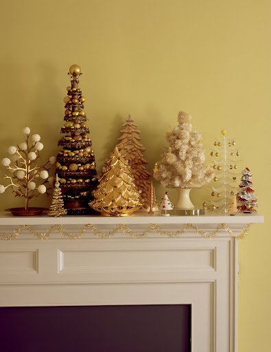 unusual and handmade trees mix with discount-store products on a mantel. The tallest is made from tin-can lids and a broomstick, and is decorated with gold balls.