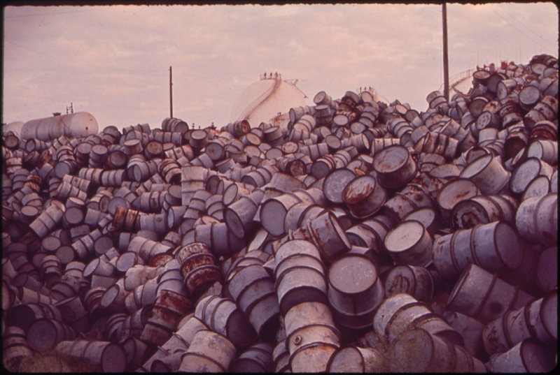 CC Photo Google Image Search Source is upload wikimedia org  Subject is A MOUNTAIN OF DAMAGED OIL DRUMS NEAR THE EXXON REFINERY NARA 546000