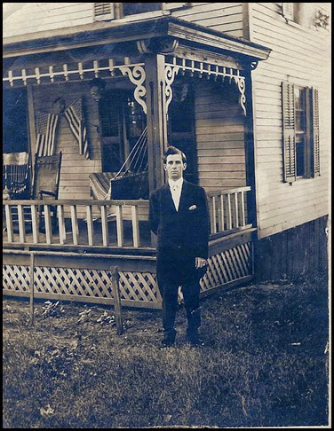 Gould_Harry in front of house with porch and flags_circa 1912