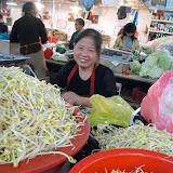 市場でモヤシを売る女性。