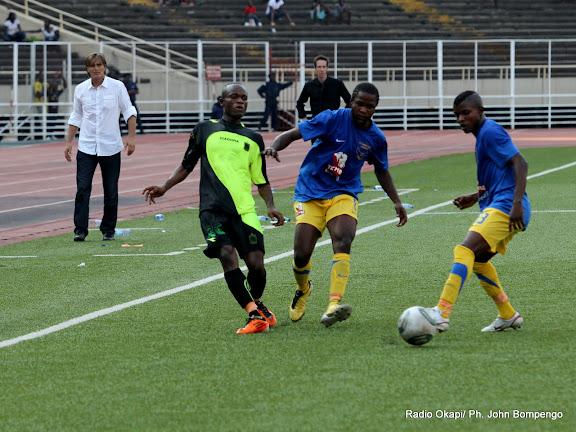 – Sous les regards de deux entraineurs en arrière plan, à gauche de Lupopo, à droite de V. Club, les joueurs (V. Club en noire et lupopo en bleu) regardent un ballon tiré ce 22/05/2011, au stade des Martyrs à Kinshasa, lors dans le cadre de Vodacom Super League dont le score final, 2 pour V. Club et 0 pour Lupopo. Radio Okapi/ Ph. John Bompengo