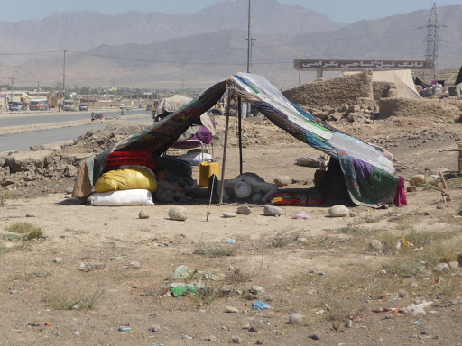 A squatter's refugee camp of war refugees has sprung along a Kabul highway. Police want the refugees to move. Here, a 70-year-old refugee says his prayers in a tent stitched together from pieces of cloth.