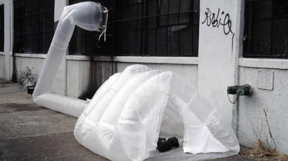 A homeless man in New York City using a unique shelter heated by exhaust from buildings, 20 December 2012. ParaSITE
