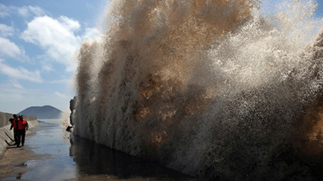 Frontier soldiers look up at the swell against a seawall as Typhoon Soulik approaches in Wenling, Zhejiang province on 12 July 2013. Photo: China Daily / Reuters