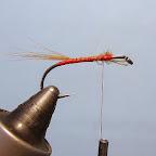 2.  Tuż za końcówką, na wysokości czubka grotu przywiązuję ogonek z pęczka promieni szyjnego pióra brązowej kury.