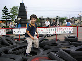 Kai on a pile of tires at the bottom of one of the big slides. Kids ride the tires down the slide.