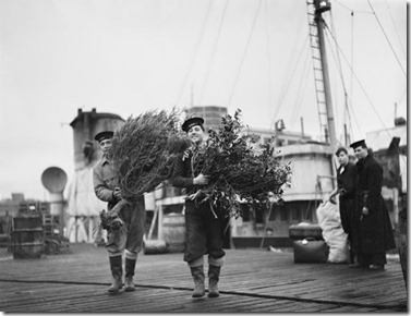 Two sailors carrying the Christm tree and holly