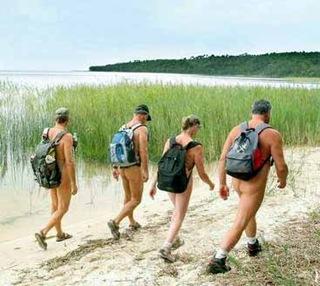 Escursionismo gruppo nudista (dietro) lungo spiaggia