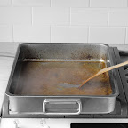 After roasting, transfer turkey to a cutting board and let rest. Place roasting pan with drippings across two burners and simmer juices, stirring with a wooden spoon, until liquid thickens and holds a trail (8-10 minutes).