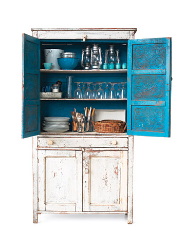 I love the distressed design of this cabinet. Notice how many of the items it houses match the beautiful blue interior of the piece. (marthastewart.com)