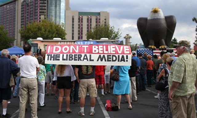 A protester holds a banner that reads, 'I don't believe the liberal media!' Conservative billionaires used a secretive funding route to channel nearly $120m (£77m) to more than 100 groups casting doubt about the science behind climate change .Climate science denial groups are mobilising against President Obama's efforts to act on climate change in his second term. Photo: Justin Sullivan / Getty Images