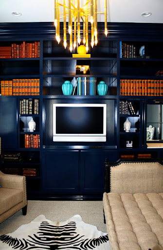 Navy blue bookcases are emboldened with sets of vintage hardback books in all ranges of oranges, browns, blues and reds. The linen furniture keeps the composition comfy. (www.domesticbliss.com)