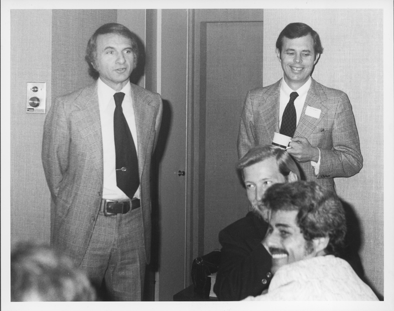 Ed Edelman (left) and John Van de Kamp stand at a breakfast held for them by gay politcal activists. 1975.