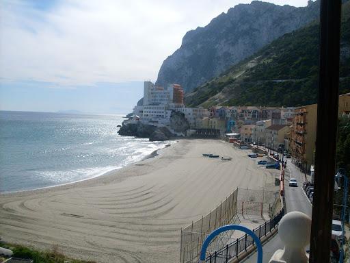 En av Gibraltars få sandstrender - nyrakt og klar for badegjester.  Atlasfjellene i Marokko i bakgrunnen til venstre for hotel Caleta.