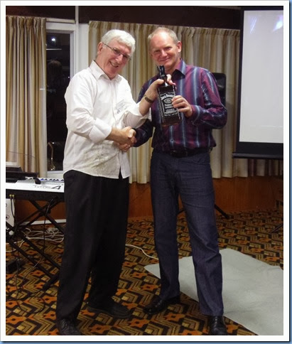 Club President, Gordon Sutherland, presenting our guest artist, Dave Hallam, with a 1.75 litre bottle of Jack Daniels, Kentucky whiskey and well earned too! Photo courtesy of Dennis Lyons.