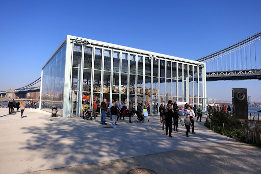 The carousel sits on the East River in Brooklyn Bridge Park, between the Brooklyn and Manhattan Bridges, housed in a spectacular acrylic pavilion, designed by French architect, Jean Nouvel.