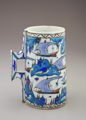 Tankard | Origin:  Iznik,  Turkey | Period: late 16th century  Ottoman period | Details:  In addition to floral, vegetal, and geometric designs, the decoration of Turkish ceramic wares from the city of Iznik occasionally features maritime imagery. The boats on this drinking vessel sail past islands accentuated by small castles, large birds, and pairs of cypress trees. Similar imagery appears in sixteenth century Turkish manuscript illustration, revealing the close connection between the arts during the Ottoman period. | Type: Composite body painted under glaze | Size: H: 21.1  W: 16.4   D: 12.3  cm | Museum Code: F1968.68 | Photograph and description taken from Freer and the Sackler (Smithsonian) Museums.