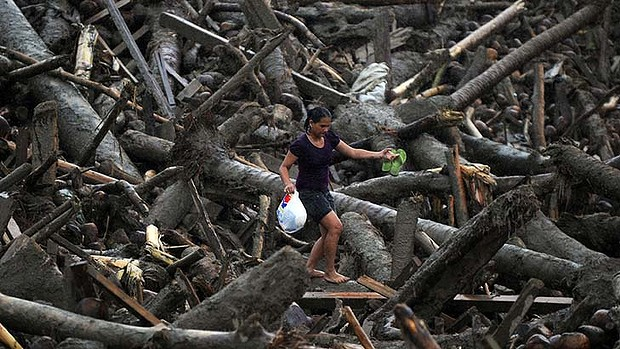 A resident of New Bataan picks through debris after receiving relief goods in the region hardest-hit by typhoon Bopha, 9 December 2012. AFP