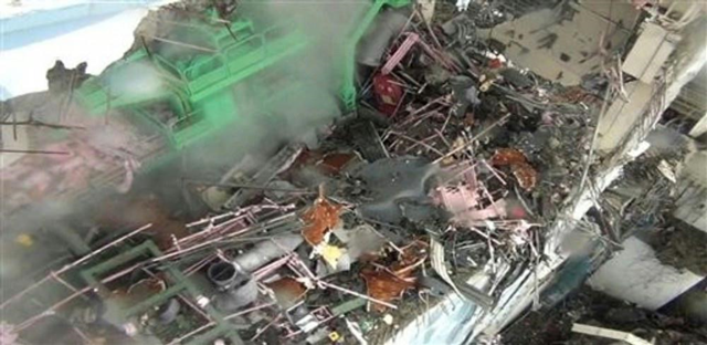 This Thursday, 24 March 2011, photo shows the inside of Unit 4 at the Fukushima Dai-ichi nuclear power plant in Okumamachi, northeastern Japan. Steam comes out of debris by a crane device, in green, at the unit. Photo: TEPCO