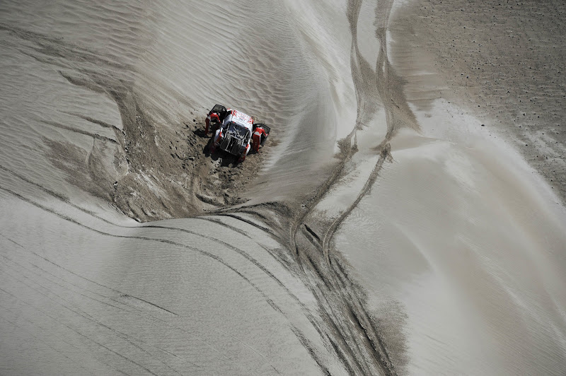 Toyota's driver Giniel De Villiers, from South Africa, and co-driver Dirk Von Zitzewitz, from Germany, try to push their car after it went off the road during the fifth stage of the 2012 Argentina-Chile-Peru Dakar Rally between Chilecito and Fiambala in Argentina, Thursday, Jan. 5, 2012. (AP Photo/Jerome Prevost, Pool)