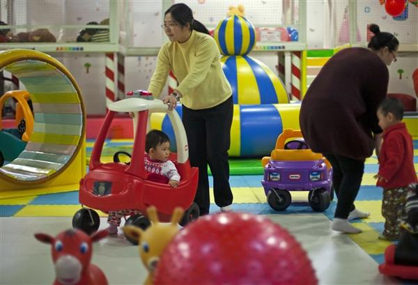 Parents play with their children at a kid's play area in a shopping mall in Beijing on 10 January 2013. Alexander F. Yuan / AP