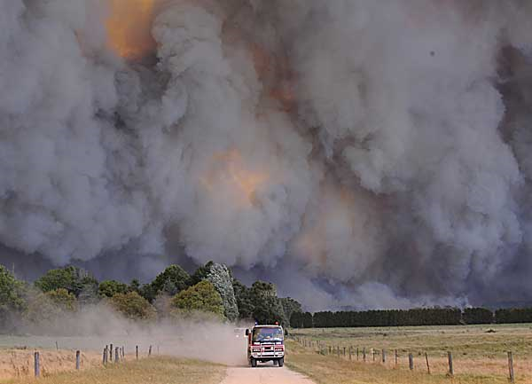 Bushfire dwarfs a fire-truck at Labertouche, near Pakenham, east of Melbourne, February 2009. Alex Coppel / The Australian