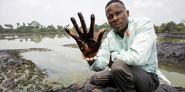 An undated image showing plaintiff Nigerian farmer Eric Dooh showing his hand covered with oil from a creek near Goi, Ogoniland, Nigeria. Photo: Marten Van Dijl / EPA
