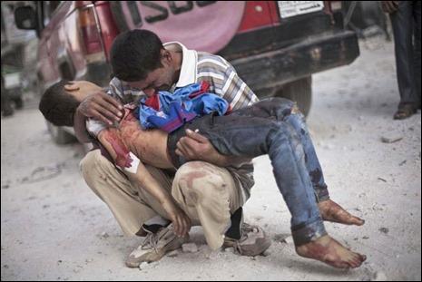 Homem chora com o cadáver do filho nos braços na Síria