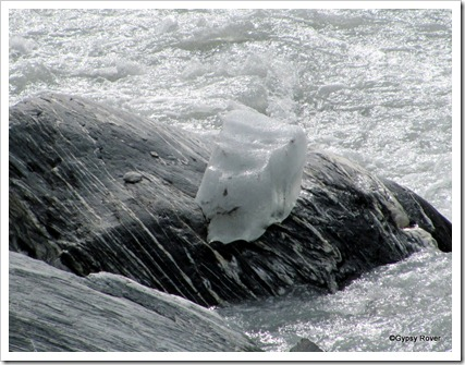 A huge ice block broken away from the Franz Josef glacier perched on a rock.