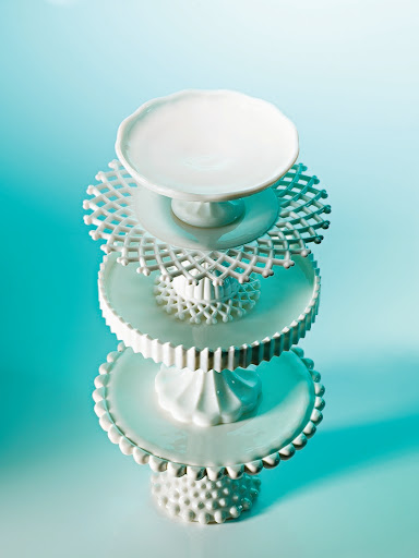 In the 18th century, European glassmakers created milk glass to mimic porcelain. After clear glass, it's the easiest to find. Some of these stands have intricate patterns on the undersides of the tops.
