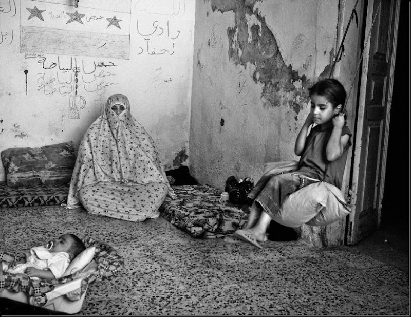 9-year-old Rania (right), sits on a swing inside her extended family's home in East Amman, an area where many Syrian refugees have rented apartments. Her father and all the men in the family are still in Syria. (Moises Saman/Magnum Photos for Save the Children)